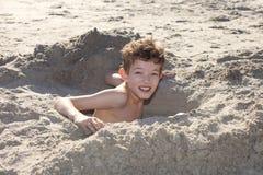 Grabendes Loch des Jungen im Sand lizenzfreie stockfotos