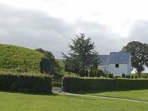 Grabhügel und Kirche beim Gelatieren in Dänemark Lizenzfreie Stockfotos