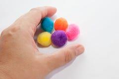 grabing五个色的球的手 库存图片