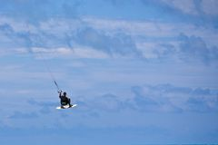grabing他的kitesurfer男的董事会 图库摄影