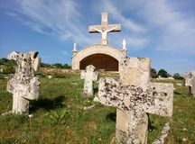 Grabovica / Bosnia and Herzegovina - June 28 2017: Catholic chapel with concrete Cross and a cementary in Eco Village, Grabovica. Grabovica / Bosnia and royalty free stock photos
