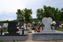Grabsteine mit Blumengaben Stockfoto