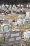 Grabstellegrundsteinmarkierung im Friedhofskirchhof mit Blumen und mehr Grundsteinen in der Hintergrundvertikale Stockbild