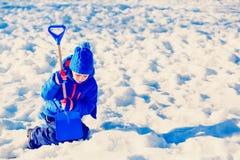 Grabung des kleinen Jungen und Spiel im Schnee, Kinderwinterbetriebe lizenzfreies stockbild