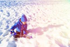 Grabung des kleinen Jungen und Spiel im Schnee, Kinderwinterbetriebe stockbild