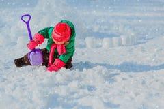 Grabung und Spiel des kleinen Mädchens im Winter schneien stockbild
