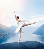Grace ballerina keep the rack in studio. Lake and mountains on background Royalty Free Stock Photos