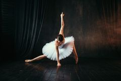 Grace of ballerina in motion on theatrical stage. Grace of ballerina in white dress in motion on theatrical stage. Classical ballet dancer training in class with Stock Image