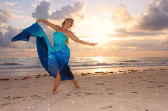 Grace on the beach. An attractive adult woman is dancing on the beach with the sun behind her , she appears to be happy and carefree Stock Photo