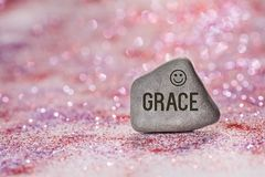 Grace engrave on stone. On shiny red and purple glitter with bokeh background stock photo