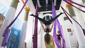 Grace women makes a gymnastic elements on the aerial hoop and silk in a studio. Slow motion stock footage