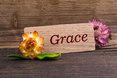 Grace word. On wooden card with dried flower on wood royalty free stock photography