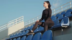 Graced young brunette sits on the blue chair and relax after morning workout on the beach slow motion. Graced young brunette sits on the blue chair and relax stock video