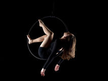 Graceful aerial dancer woman on black. Graceful aerial dancer woman doing her performance with a hoop on black stock photo