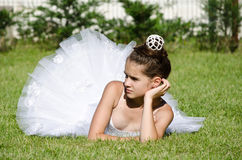 Graceful ballerina. Sitting on the grass and poses Stock Image