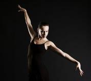 Graceful ballerina. Against dark background Stock Photo