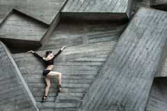 Graceful ballerina. On the background of the concrete urban structure. Dancer dressed in a black leotard and tights Royalty Free Stock Photo