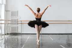 Graceful ballerina dance in ballet class. Barrre and white wall on background royalty free stock image