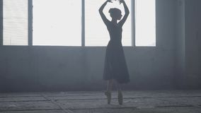 Graceful ballerina dancing in black dress in the studio in front of a large window. Young beautiful ballet dancer stock video