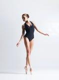 Graceful ballerina dancing in a studio. Graceful ballerina dancing in art performance. Young and beautiful ballet dancer Stock Photos