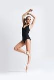 Graceful ballerina dancing in a studio. Graceful ballerina dancing in art performance. Young and beautiful ballet dancer Royalty Free Stock Photography