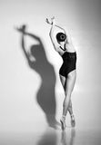 Graceful ballerina dancing in a studio. Graceful ballerina dancing in art performance. Young and beautiful ballet dancer in black and white Stock Photography
