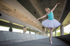 Graceful ballerina doing dance exercises on a. Concrete bridge against the backdrop of the prospects of support columns Royalty Free Stock Images