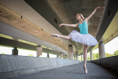 Graceful ballerina doing dance exercises on a. Concrete bridge against the backdrop of the prospects of support columns Stock Photo