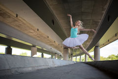 Graceful ballerina doing dance exercises on a. Concrete bridge against the backdrop of the prospects of support columns Royalty Free Stock Photo