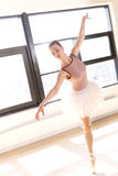 Graceful Ballerina en Pointe in Dance Studio. Full Length of Graceful Young Ballerina Wearing Pink Tutu en Pointe in Sunny Dance Studio Stock Photos