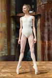 Graceful ballerina on pointe against a background. Graceful ballerina in a white bathing suit standing on pointe against a background rusty background, bridge Stock Images