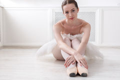 Graceful Ballerina sit on floor, ballet background. Beautiful graceful young ballerina in pointe shoes sit at white wooden floor. Ballet practice of classical Royalty Free Stock Image