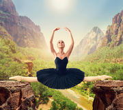 Graceful ballerina sit on the twine over the gorge. Mountain valley on background Stock Photo
