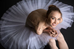 Graceful ballerina sitting on the floor. Young, graceful ballerina sitting on the floor on a black background in the studio looking at the top of the camera with Royalty Free Stock Photography