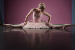 Graceful ballerina sitting with legs stretched out Stock Image