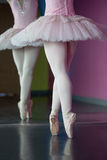 Graceful ballerina standing en pointe in front of mirror Stock Photo