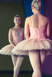 Graceful ballerina standing in first position in front of mirror Stock Images