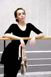 Graceful ballerina standing near the ballet barre in a beautiful Stock Images