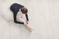 Graceful Ballerina stretching, ballet background, top view. Beautiful graceful young ballerina in pointe shoes at white wooden floor background, top view from Royalty Free Stock Images