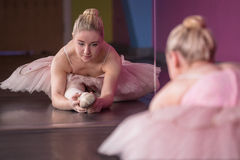 Graceful ballerina warming up in front of mirror Royalty Free Stock Photo