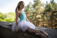 Graceful ballerina in white tutu sitting on the Stock Images
