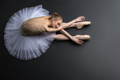 Graceful ballerina. Young, graceful ballerina sitting on the floor on a black background in a studio in the slope face touching knees Royalty Free Stock Images