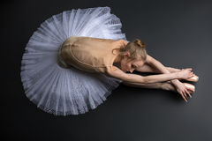 Graceful ballerina. Young, graceful ballerina sitting on the floor on a black background in a studio in the slope face touching knees Royalty Free Stock Photography