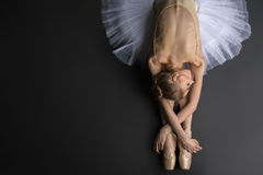 Graceful ballerina. Young, graceful ballerina sitting on the floor on a black background in a studio in the slope face touching knees. Close-up Royalty Free Stock Photos