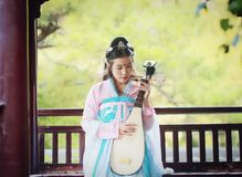 Elegant woman in Chinese traditional drama ancient costume play Chinese lute pipa guitar. Graceful and beautiful chinese girl in hanfu dress, play pipa chinese Royalty Free Stock Photography
