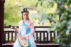Elegant woman in Chinese traditional drama ancient costume play Chinese lute pipa guitar. Graceful and beautiful chinese girl in hanfu dress, play pipa chinese Royalty Free Stock Photo