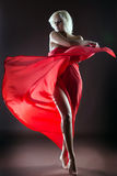 Graceful blonde dancing naked with red cloth. In studio Stock Photos