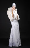 Graceful bride wrapping up in fur coat. Stock Images