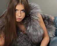 Graceful brunette posing in jeans and fur Stock Images