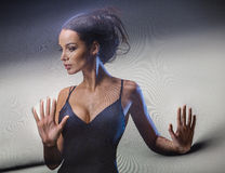 Graceful brunette stretches stretch mesh fabric in front of you Royalty Free Stock Images